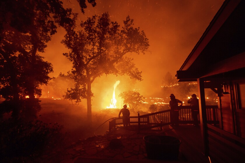 FILE - In this Aug. 21, 2020, file photo, firefighters watch flames from the LNU Lightning Complex fires approach a home in the Berryessa Estates neighborhood of unincorporated Napa County, Calif. The blaze, the fifth largest in California history, forced thousands to flee and destroyed more than 1,000 homes and other structures. This year has seen record Atlantic hurricanes and western wildfires, devastating floods in Asia and Africa and a hot, melting Arctic. It's not just been a disastrous year, but a year of disasters. (AP Photo/Noah Berger, File)
