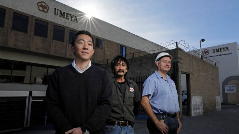Rex Hamano, left, is the third generation to run Umeya Rice Cake Co. in Los Angeles. With him are longtime workers Clemence Santos, center, and Adan Medina. The company will be closing at the end of the year after 92 years in business.
