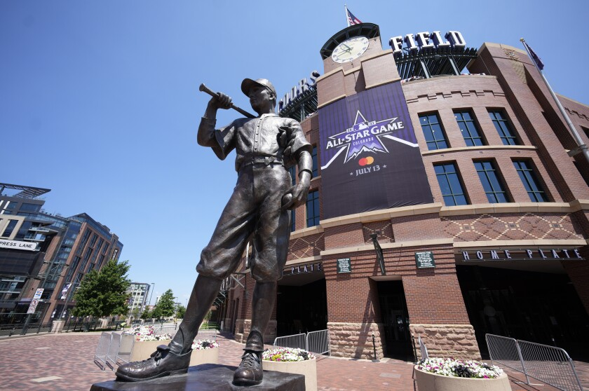 """A banner for the All-Star game hangs on the front of Coors Field near the sculpture entitled """"The Player"""" after a news conference to kick off All-Star week Wednesday, July 7, 2021, in Denver. (AP Photo/David Zalubowski)"""