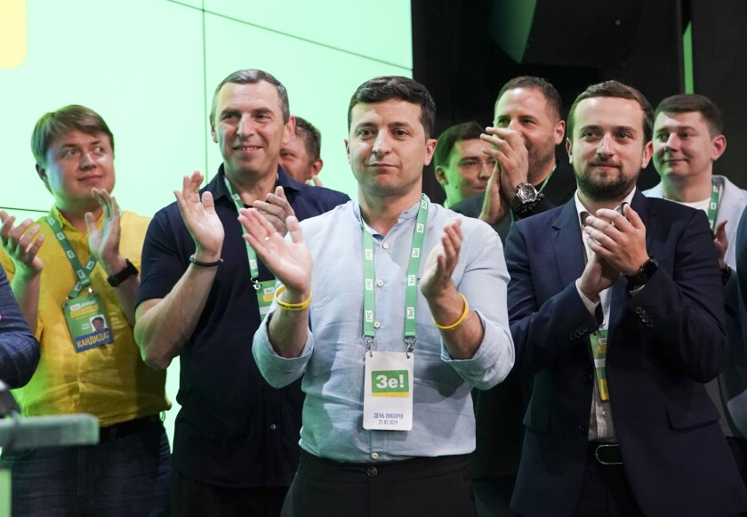 Ukrainian President Volodymyr Zelensky, center, monitors election results at his party's headquarters in the capital, Kiev.