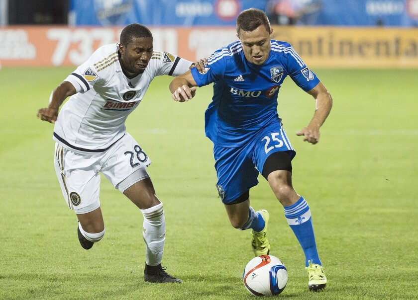 Montreal Impact's Donny Toia, right, challenges Philadelphia Union's Raymon Gaddis during the first half of a MLS soccer game, Saturday, Aug. 22, 2015 in Montreal. (Graham Hughes/The Canadian Press via AP) MANDATORY CREDIT