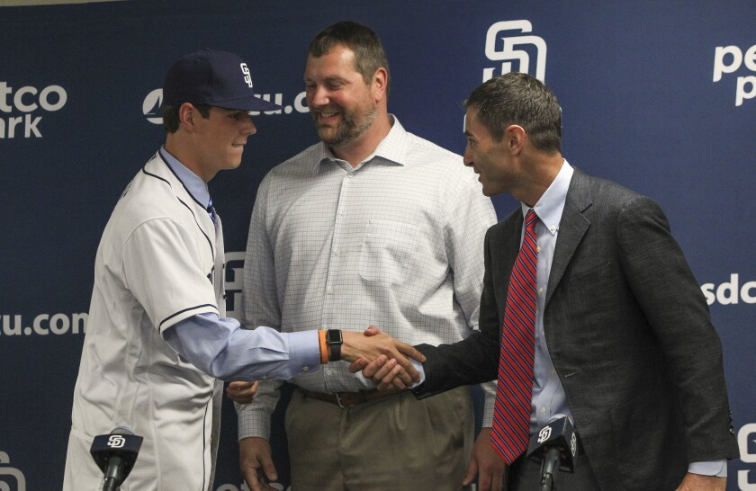 Padres first-round draft pick left hand pitcher MacKenzie Gore shakes hands with Padres general manager A.J. Preller with Padres scouting director Mark Conner in between during a press conference at Petco Park in 2017.