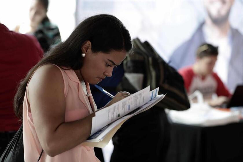 Una joven mexicana estudiante de ingeniería completa un formulario en una feria de trabajo. EFE/Archivo