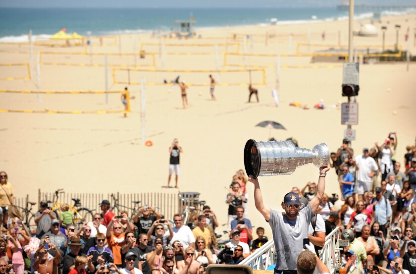 Then-Kings center Jarrett Stoll raises the Stanley Cup among a crowd of fans at Hermosa Beach.