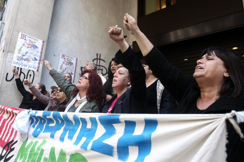 Laid-off cleaners protest at the Athens headquarters of their former employer, the Greek Finance Ministry, which is under scrutiny over millions of dollars it gave to nongovernmental organizations.