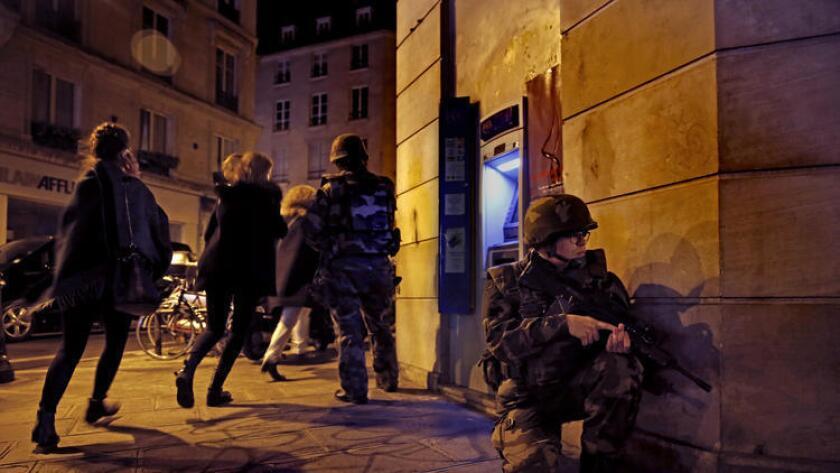 Una mujer corre a un lado de los soldados franceses, mientras el pánico se extiende en las calle sde París.