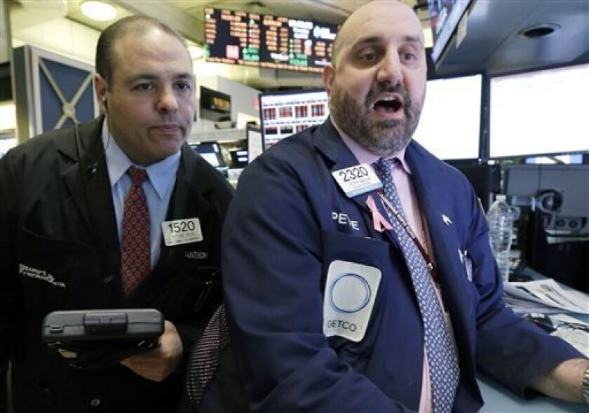 In this Thursday, April 4, 2013, photo, Trader Anthony Riccio, left, and specialist Peter Giacchi work on the floor of the New York Stock Exchange. Japan's benchmark stock index surged to its highest level in more than four years Friday April 5, 2013, its second straight day of big gains after the central bank announced aggressive action to lift the economy out of a prolonged slump. European stocks fell in early trading. (AP Photo/Richard Drew)