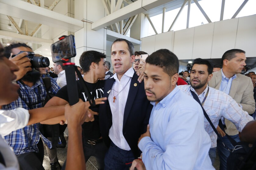 Opposition leader Juan Guaido arrives to the Simon Bolivar International Airport in La Guaira, Venezuela, Tuesday, Feb. 11, 2020. Guaido returned home from a tour of nations that back his effort to oust socialist leader Nicolás Maduro. (AP Photo/Ariana Cubillos)