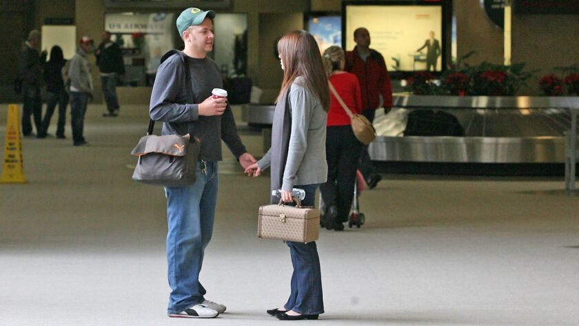 BACK HOME – A couple arrives at John Wayne Airport Wendnesday, where the crowds were considered ligh