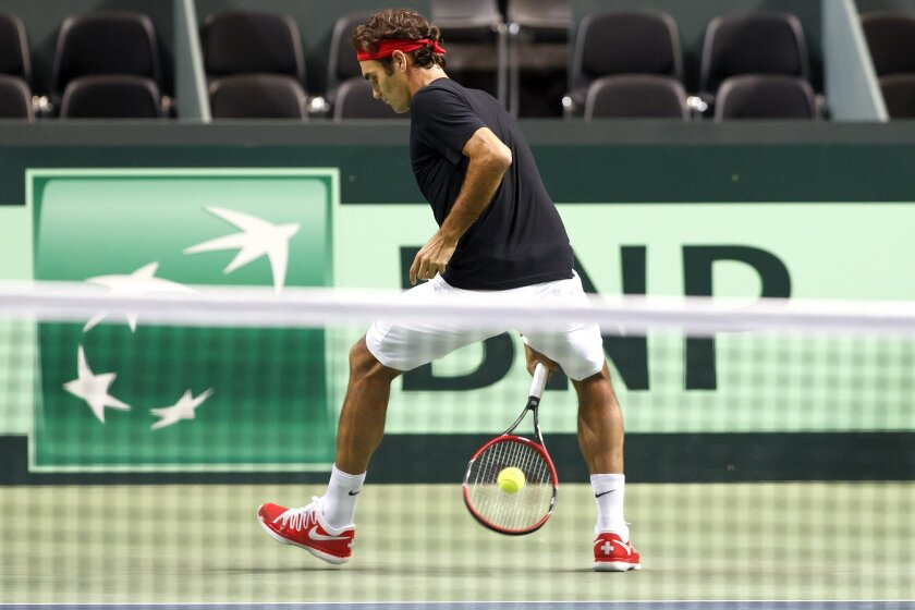 Roger Federer, of Switzerland, returns a ball, during a training session of the Swiss Davis Cup Team prior to the Davis Cup World Group Semifinal match between Switzerland and Italy, at Palexpo, in Geneva, Switzerland, Tuesday, Sept.9, 2014. The Davis Cup World Group Semifinal Switzerland vs Italy will take place from 12 to September 14. (KEYSTONE/Salvatore Di Nolfi)