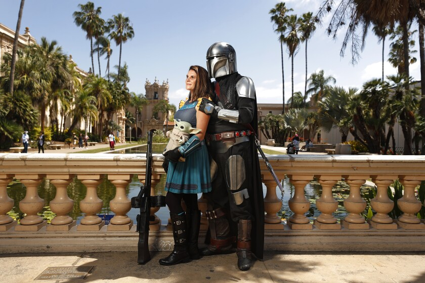 Shawn Richter dressed as The Mandalorian and his fiance Lisa Lower as Cara Dune with Yoda