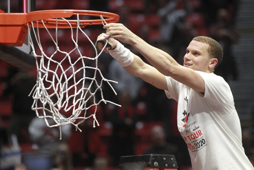 SDSU guard Malachi Flynn takes his turn to cut the net after the Aztecs defeated New Mexico 82-59 at Viejas Arena on Tuesday.