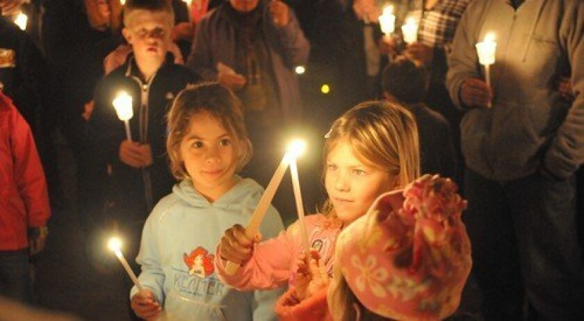 Trinity Phillips lights a candle for sister India. Photo: Rob McKenzie