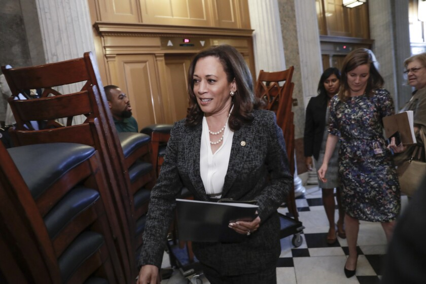 Sen. Kamala Harris, carrying a notebook, walks past stacked chairs.
