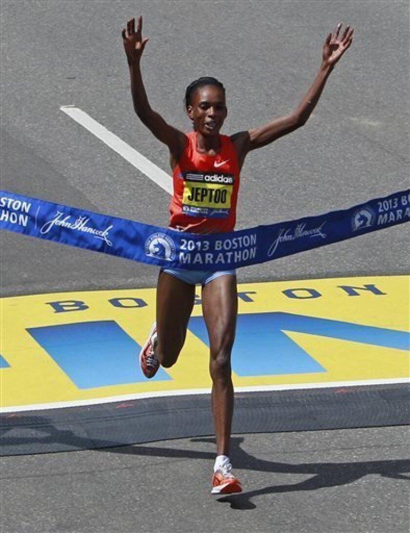 Rita Jeptoo, of Kenya, crosses the finish line to win the women's division of the 2013 running of the Boston Marathon in Boston, Monday, April 15, 2013. (AP Photo/Charles Krupa)