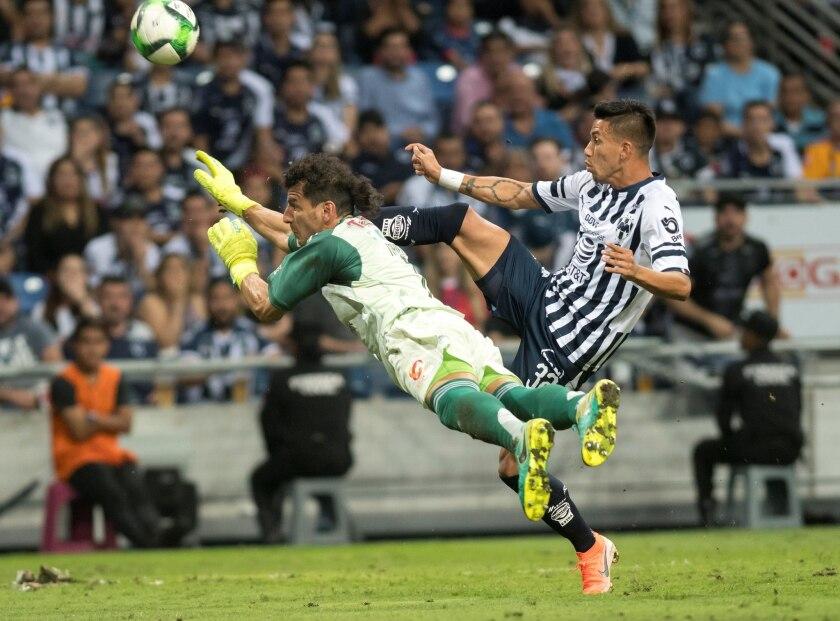 Maximiliano Meza (d) de Rayados de Monterrey disputa el balón con Nahuel Guzman (i) portero de Tigres este miércoles, durante un partido correspondiente a la ida de la semifinal del Torneo Clausura 2019, celebrado en el estadio BBVA de la ciudad de Monterrey (México).