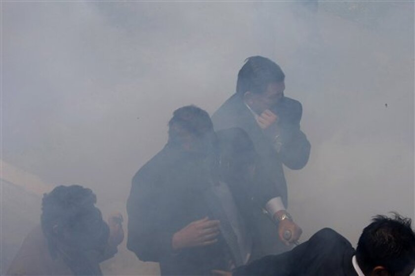 Wearing a gas mask, Ecuador's President Rafael Correa, center, is escorted by bodyguards as he run away from tear gas during a protest of police officers and soldiers against a new law that cuts their benefits at a police base in Quito, Ecuador, Thursday, Sept. 30, 2010. Correa tried to speak with