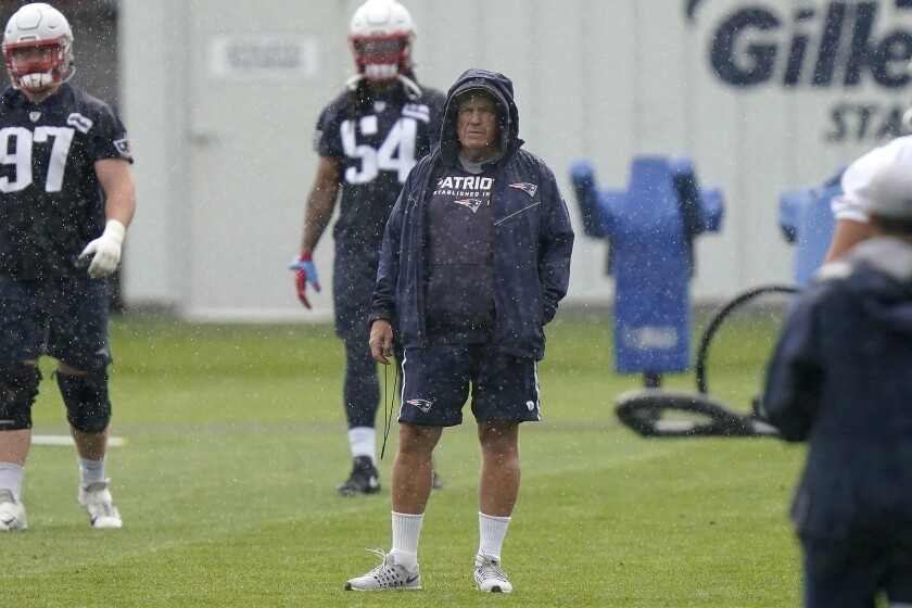 New England Patriots head coach Bill Belichick, center, stands on the field during an NFL football practice, Monday, June 14, 2021, in Foxborough, Mass. (AP Photo/Steven Senne)