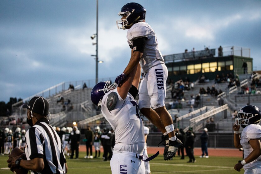 Carlsbad running back Mazlo Norwood is lifted in celebration after scoring a touchdown.
