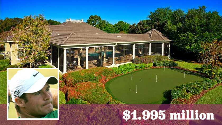 A putting green sits in between a covered patio and the Tom Fazio-designed golf course.