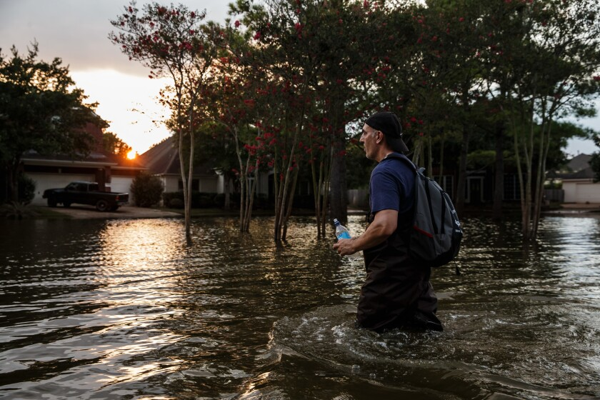 Samir Novruzov wades through water to get to a vehicle after spending the day clearing out his flooded home in Katy, Texas.