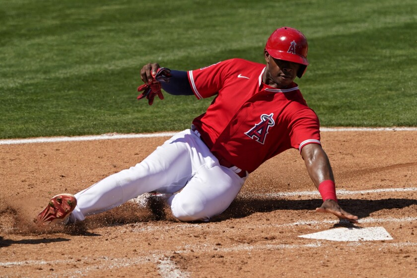 Angels outfielder Justin Upton slides into home plate to score on a hit by Kurt Suzuki.