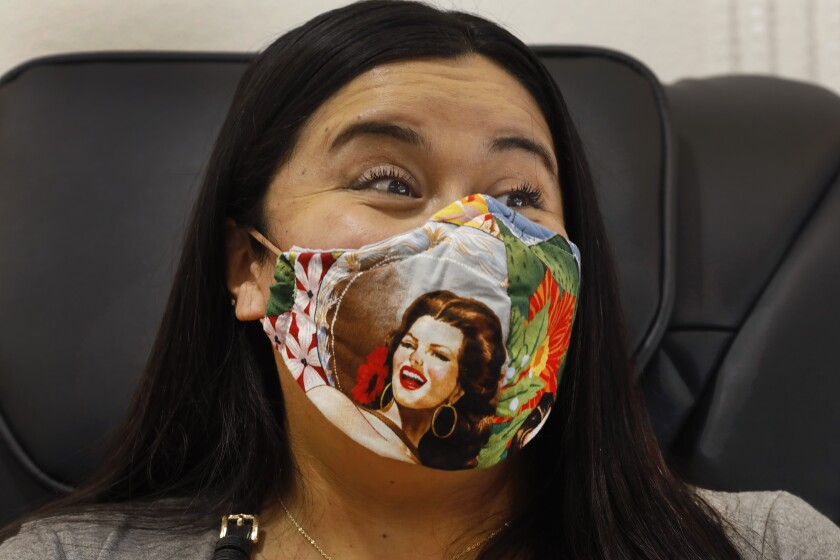 Brittney Robertson wears her face mask while getting her nails done.