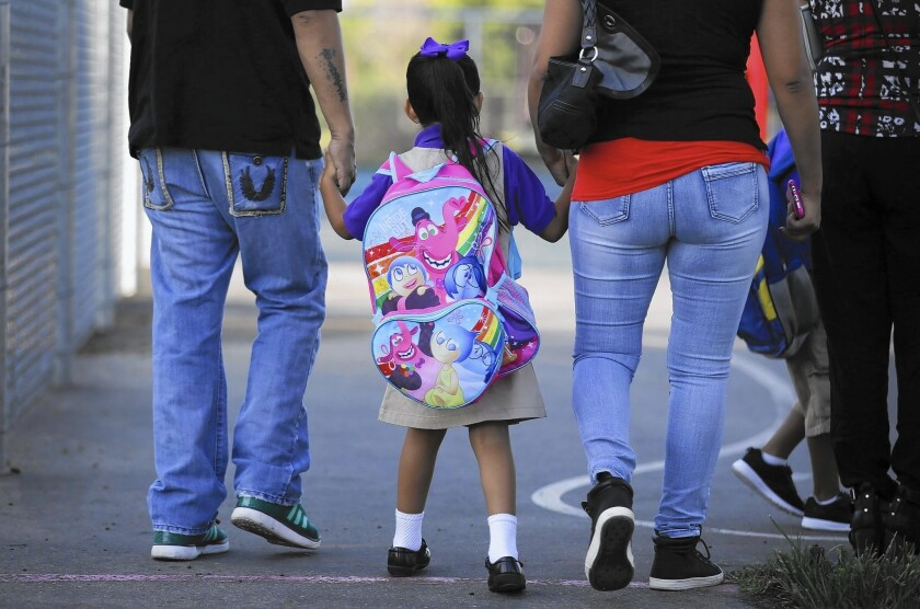 Parents walk their daughter to class on the first day of kindergarten at the Telesis Academy in West Covina on Aug. 17, 2015.