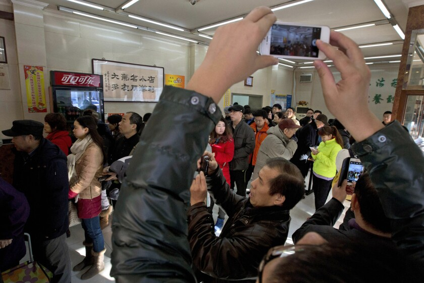 Smartphone users take photos in a Beijing restaurant where President Xi Jinping lined up the day before to order a simple lunch of steamed buns, vegetables and stewed pig intestines.