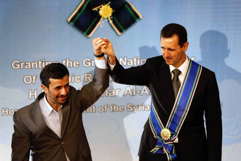 In this photo from 2010, Iranian President Mahmoud Ahmadinejad, left, stands with Syrian President Bashar Assad. With Assad's regime increasingly unstable, the partnership may be fracturing.