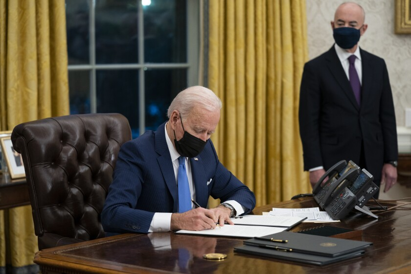 FILE - In this Tuesday, Feb. 2, 2021, file photo, Secretary of Homeland Security Alejandro Mayorkas looks on as President Joe Biden signs an executive order on immigration, in the Oval Office of the White House in Washington. Biden, under political pressure, agreed to admit four times as many refugees this budget year as his predecessor did, but resettlement agencies concede the number actually allowed into the U.S. will be closer to the record-low cap of 15,000 set by former President Donald Trump. (AP Photo/Evan Vucci, File)