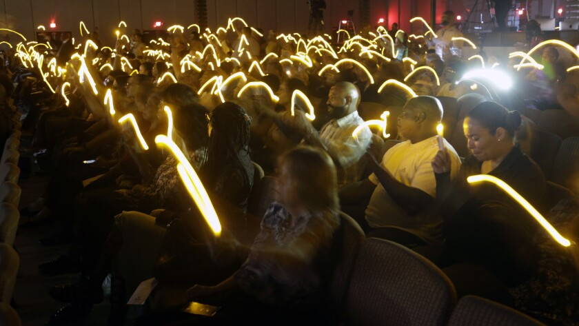 Mourners hold electric candles at a vigil Monday for Robert Hollis, who was found dead last week in his Inglewood apartment.