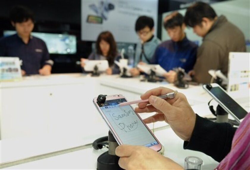 In this April 10, 2013 photo, a customer doodles on a new Samsung smartphone at a retail shop in Taipei, Taiwan. Taiwanese companies have long viewed tech giant Samsung as a major threat and the battle has recently appeared to tilt in favor of the South Korean rival as Taiwan's smartphone, memory chip and display panel makers suffered sagging exports. The sales erosion has been driven by competition, some of it from South Korea, and a weak global economy but has also spawned fears on this export