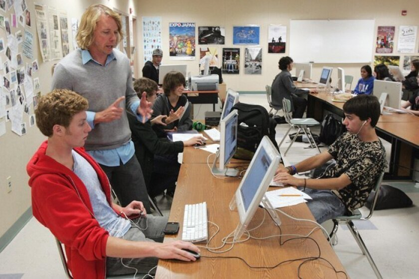 Student Reid McCallum (seated left) works with film teacher Mark Raines on a project about Haiti at Canyon Crest Academy.