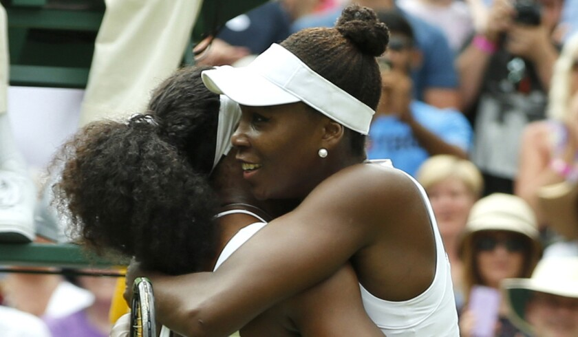 Serena Williams, left, hugs her sister Venus Williams after winning their singles match at Wimbledon on July 6.