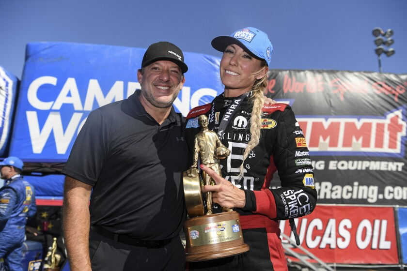 In this photo provided by the NHRA, Top Fuel driver Leah Pruett celebrates her Auto Club Raceway at Pomona auto race win with fiancé Tony Stewart, Sunday, Aug. 1, 2021, in Pomona, Calif. Pruett took home her first title of the season on Sunday when she cruised to a 4.021-second lap at 247.61 mph in her Sparkling Ice Spiked Top Fuel dragster. (Jerry Foss/NHRA via AP)