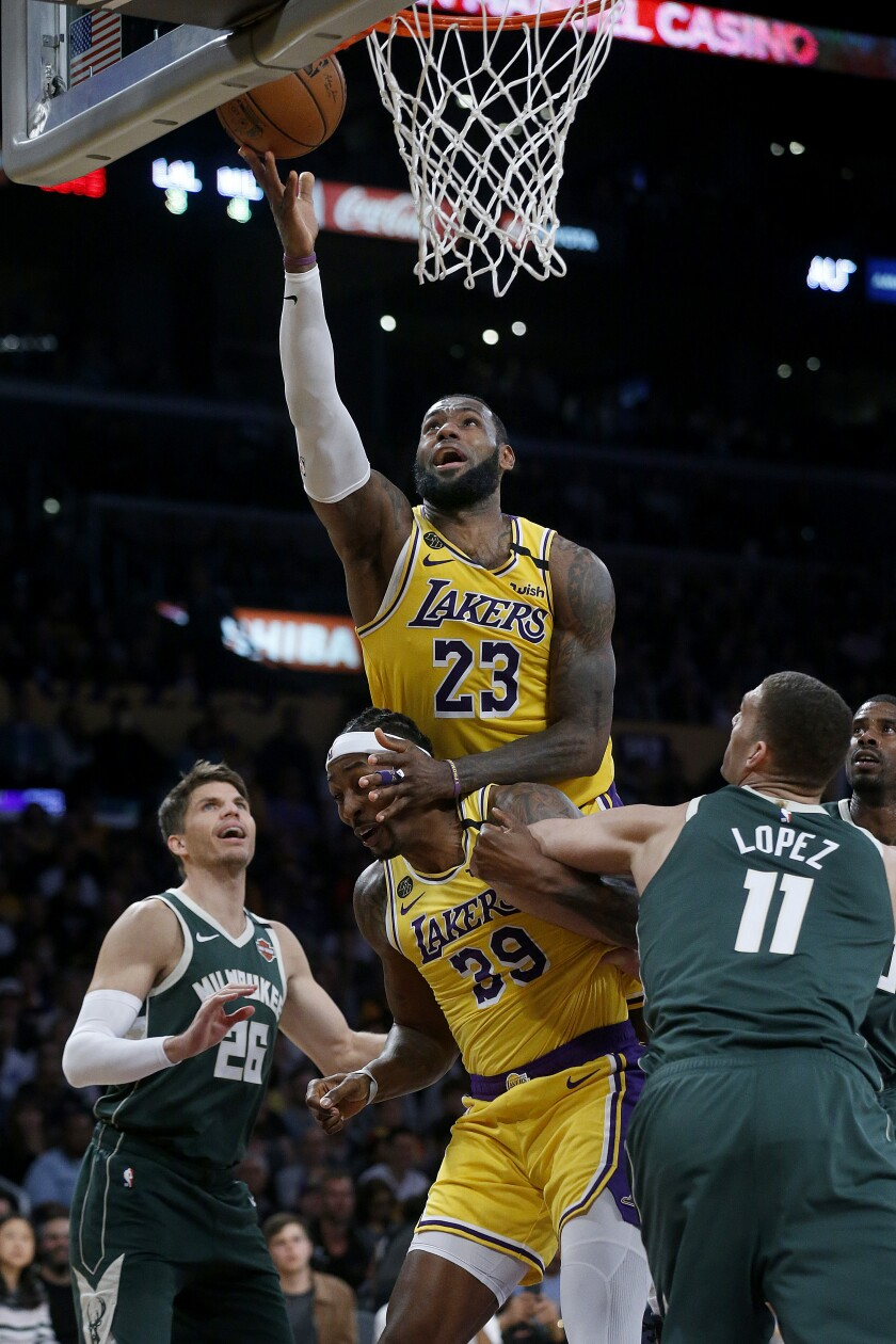 LeBron James scores a basket from Dwight Howard's back during the second half of the Lakers' victory over the Bucks on March 6 at Staples Center.