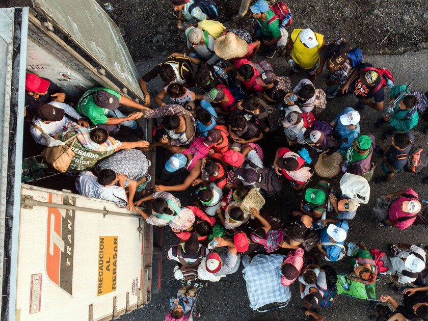 Honduran migrants taking part in a caravan heading to the U.S., get on a truck near Pijijiapan, Mexico.