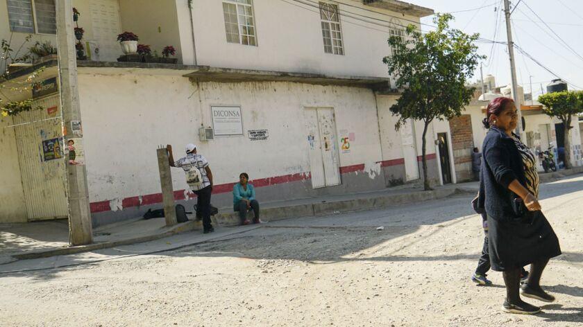 Locals cross the street in Lo De Juarez, a small community in Guanajuato. Hundreds of nearby auto fa