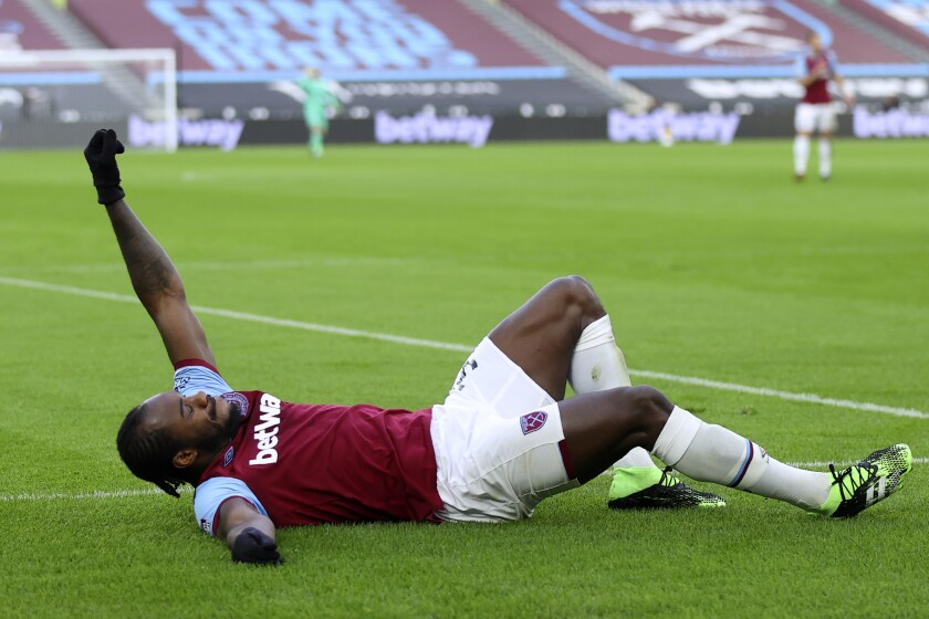 West Ham's Michail Antonio celebrates on the ground after scoring the opening goal during the English Premier League soccer match between West Ham United and Burnley, at London stadium, in London, Saturday, Jan. 16, 2021. (Julian Finney/Pool via AP)