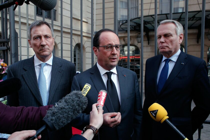 France's President Francois Hollande, center, addresses the medias while Belgium Ambassador to France Vincent Mertens de Wilmars, left, and French foreign minister Jean-Marc Ayrault look on, outside the Belgian embassy, in Paris, Tuesday, March 22, 2016. Bombs exploded at the Brussels airport and one of the city's metro stations Tuesday, killing and wounding dozens of people, as a European capital was again locked down amid heightened security threats. (AP Photo/Thibault Camus)