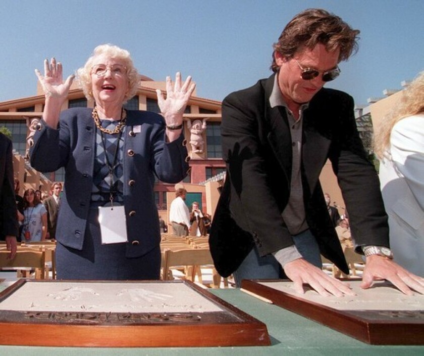 Virginia Davis and Kurt Russell make molds of their handprints as part of Disney's 75th anniversary celebration in 1998.