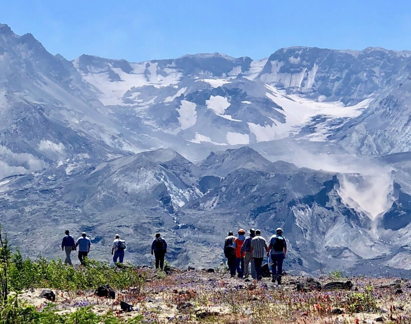 The Mt. St. Helens crater towers above hikers.