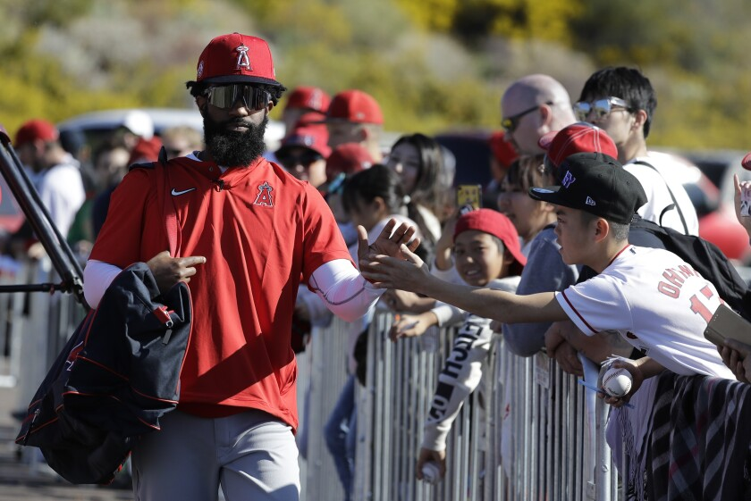 Angels' Brian Goodwin, left, greets a fan during spring training baseball practice on Monday in Tempe, Ariz.