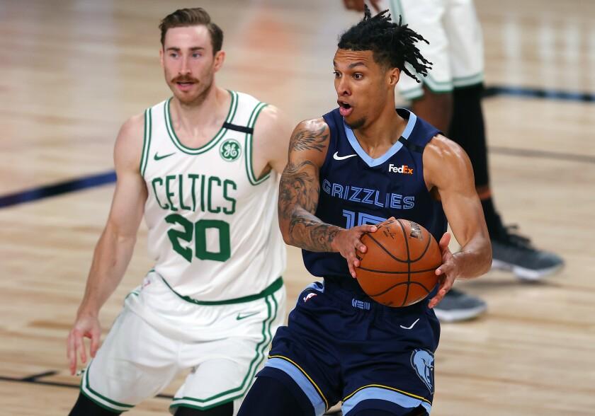 Memphis Grizzlies' Brandon Clarke (15) handles the ball as Boston Celtics' Gordon Hayward (20) defends during the second half of an NBA basketball game Tuesday, Aug. 11, 2020, in Lake Buena Vista, Fla. (AP Photo/Mike Ehrmann, Pool)