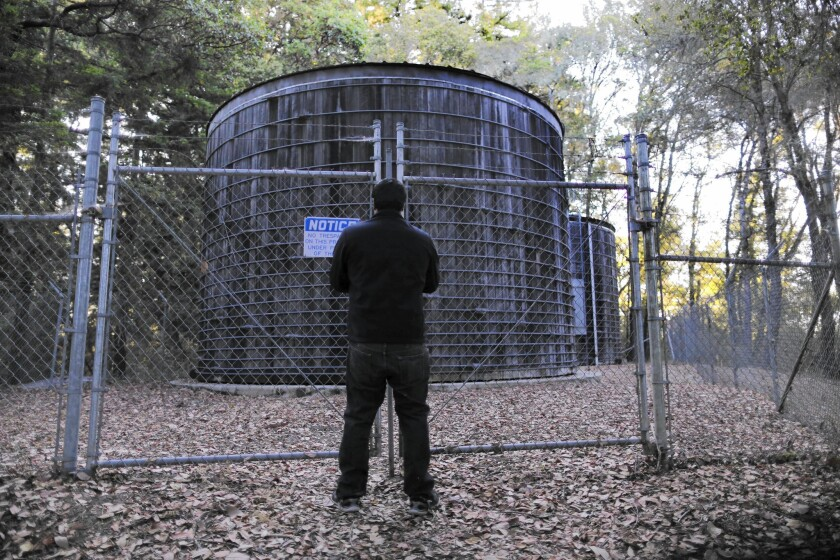 Ricardo Villa, a water district employee, locks a gate after checking redwood water tanks.