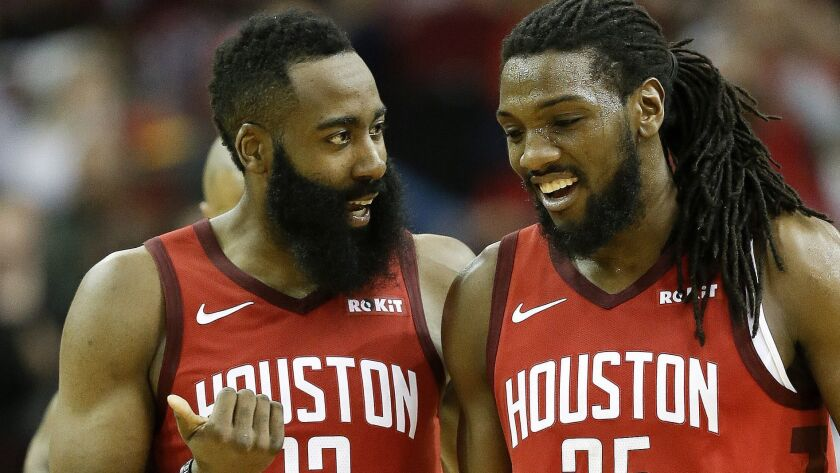 Rockets guard James Harden (13) talks with forward Kenneth Faried late in the second half of a game against the Raptors on Friday.