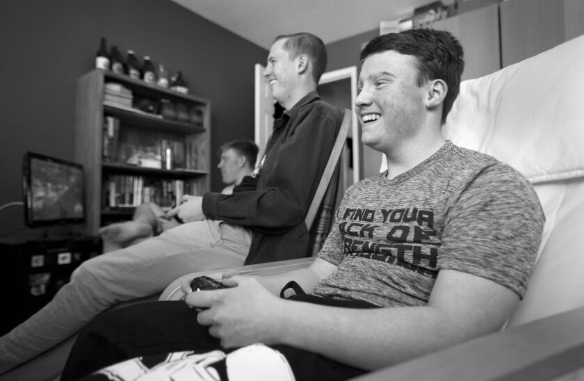 """Looking forward to the opening night showing of """"The Force Awakens,"""" Sam and his friends Tim Wazny and Chayson Roberts play Star Wars video games at Tim's home."""