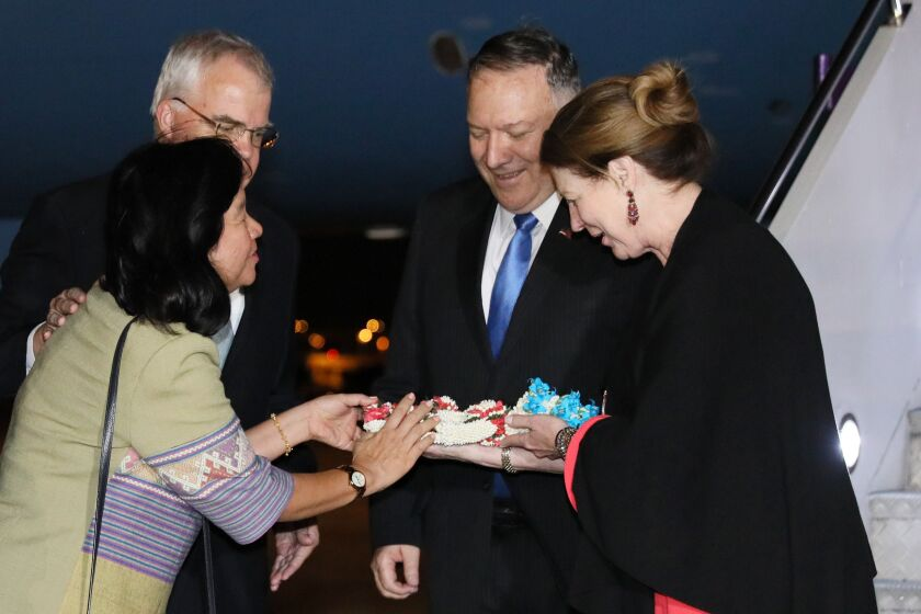Secretary of State Michael R. Pompeo and his wife, Susan, right, are greeted with flowers by U.S. Embassy Chargé d'Affaires Peter Haymond and his wife, Dusadee, as they arrive at Don Mueang International Airport in Bangkok, Thailand, on Thursday.