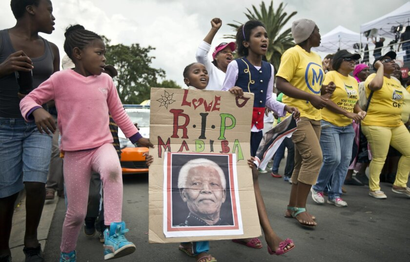 "A young girl with a placard showing the face of Nelson Mandela and referring to his clan name ""Madiba"", marches with others to celebrate his life, in the street outside his old house in Soweto, Johannesburg, South Africa, Friday, Dec. 6, 2013. Flags were lowered to half-staff and people in black townships, in upscale mostly white suburbs and in South Africa's vast rural grasslands commemorated Nelson Mandela with song, tears and prayers on Friday while pledging to adhere to the values of unity and democracy that he embodied. (AP Photo/Ben Curtis)"